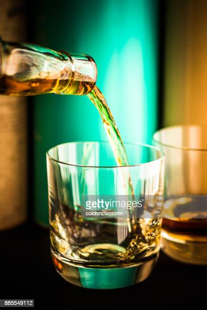 whisky being poured from clear glass bottle into glass tumbler with scotch malt whisky bottles in background - liqueur stock pictures, royalty-free photos & images