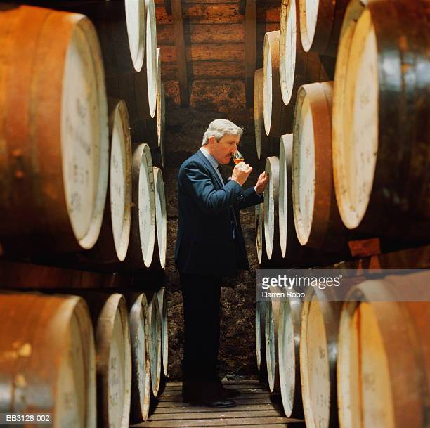 whisky distillation, blender sampling from storage cask - distillery stock pictures, royalty-free photos & images