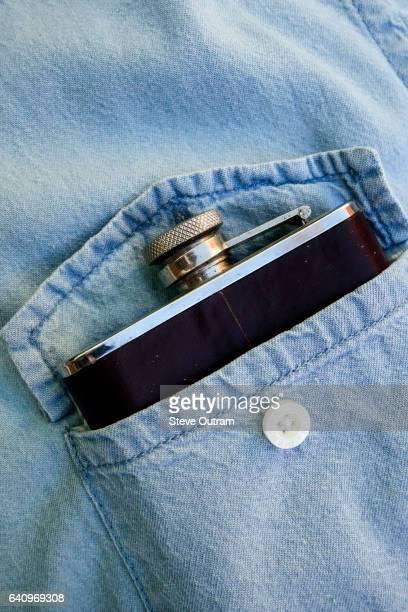 Whisky flask in denim shirt pocket