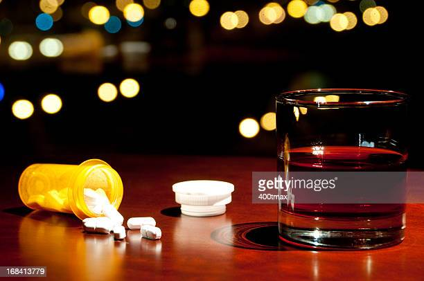 whisky or rum and a bottle of spilled pills - alcohol drink stock pictures, royalty-free photos & images