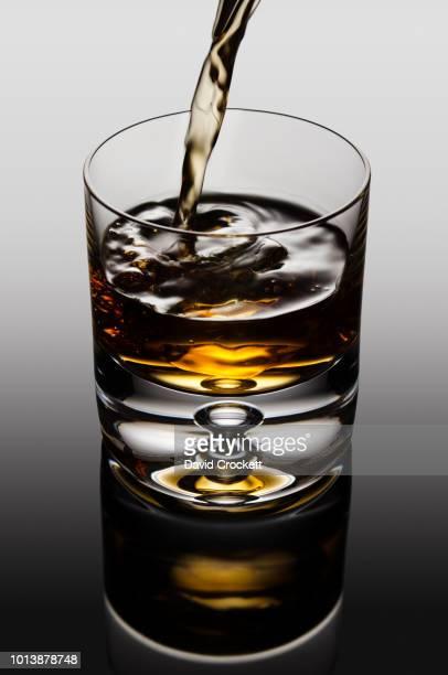 whisky pour - bourbon whiskey stock-fotos und bilder