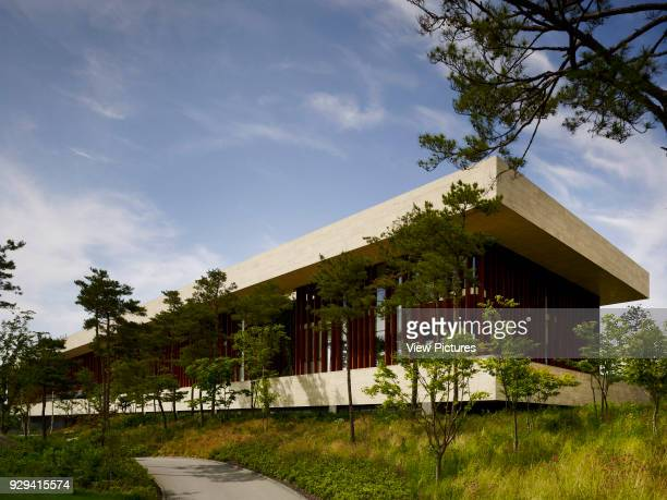 Whistling Rock Golf Clubhouse, Chuncheon, Korea, South. Architect: Mecanoo, 2012. Building in perspective with walkway and spruce trees.