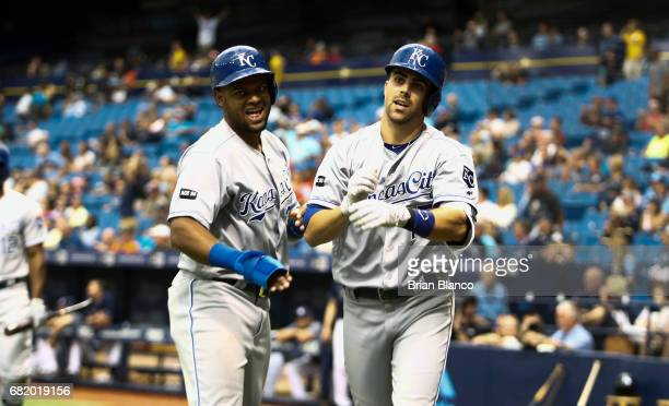 Whit Merrifield of the Kansas City Royals celebrates with Jorge Bonifacio after both scoring off of Merrifield's single and the subsequent error by...