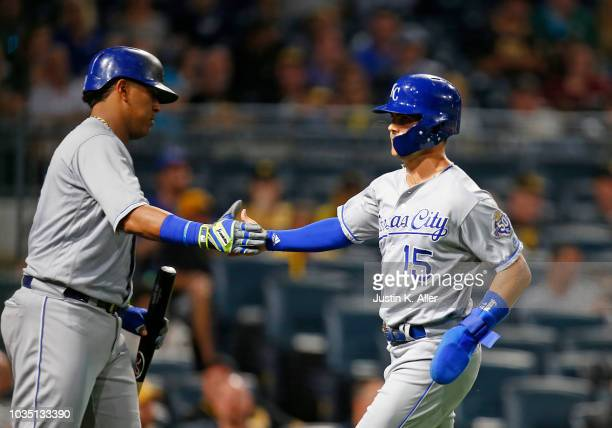 Whit Merrifield of the Kansas City Royals celebrates with Salvador Perez after scoring on an RBI double in the third inning against the Pittsburgh...