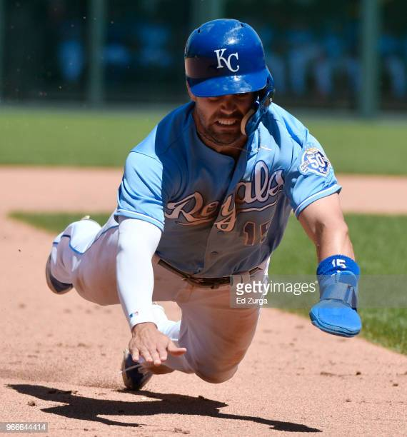 Whit Merrifield of the Kansas City Royals dives into third for a steal against the Oakland Athletics in the sixth inning at Kauffman Stadium on June...