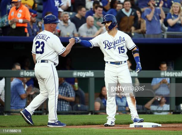 Whit Merrifield of the Kansas City Royals is congratulaed by third base coach Mike Jirschele after hitting a triple during the 1st inning of the game...