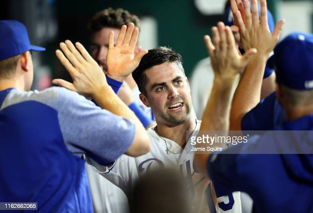 Whit Merrifield of the Kansas City Royals is congratulated by teammates in the dugout after scoring during the 5th inning of the game against the...