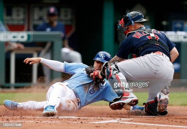 Whit Merrifield of the Kansas City Royals is tagged out at home plate by catcher Christian Vazquez of the Boston Red Sox during the 1st inning of the...