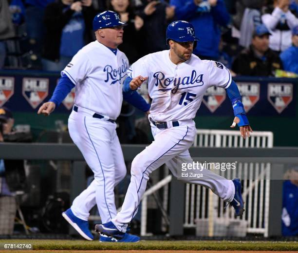 Whit Merrifield of the Kansas City Royals runs past Mike Jirschele as he heads home to score on a Mike Moustakas double in the sixth inning against...