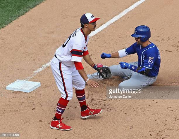 Whit Merrifield of the Kansas City Royals slides into third base after hiting a two run triple in the 6th inning as Tyler Saladino of the Chicago...