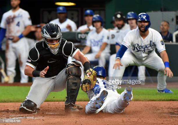 Whit Merrifield of the Kansas City Royals slides past catcher James McCann of the Chicago White Sox for a tworun insidethepark home run in the fourth...
