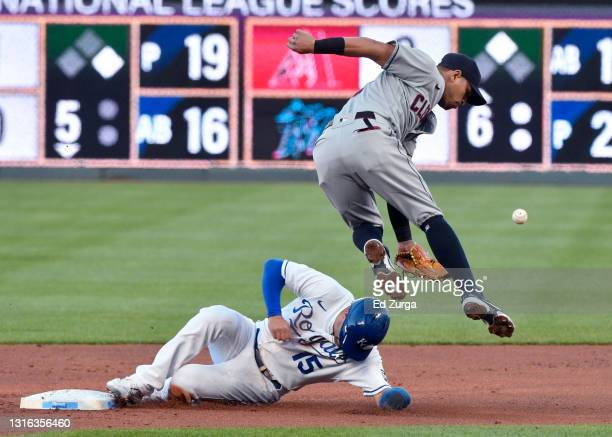 Whit Merrifield of the Kansas City Royals slides under second baseman Cesar Hernandez of the Cleveland Indians for a steal in the first inning at...