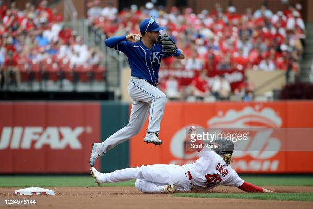 Whit Merrifield of the Kansas City Royals turns a double play over Harrison Bader of the St. Louis Cardinals during the second inning at Busch...