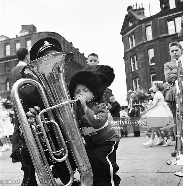 Patrick Rooney aged 4 tries his hand at a big blow whilst waiting for his Sunday School to move off Watching is bandsman Dennis Barlow Greater...