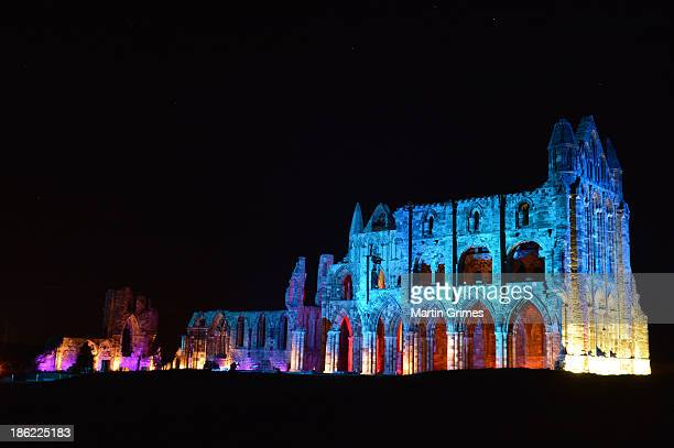 Whitby Abbey is illuminated for Whitby's Goth weekend where night time visitors walk amongst the ruins which inspired Bram Stoker's Dracula while...