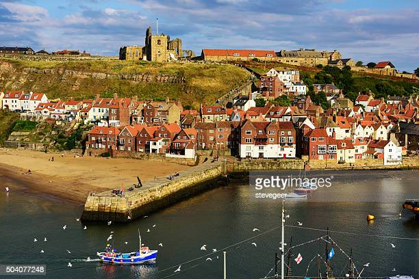 whitby  church, town,  abbey, harbour wall and beach - whitby north yorkshire england stock photos and pictures