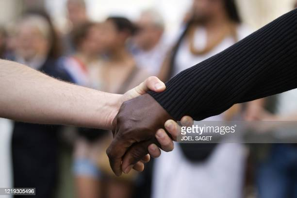 White and a black person hold hands as they take part in a march in Paris, on March 25, 2012. This demonstration was called by human rights...