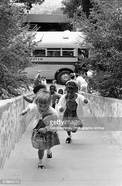 White and African American children come up a flight of stairs from the school bus on the first day of school desegregation in Berkeley California