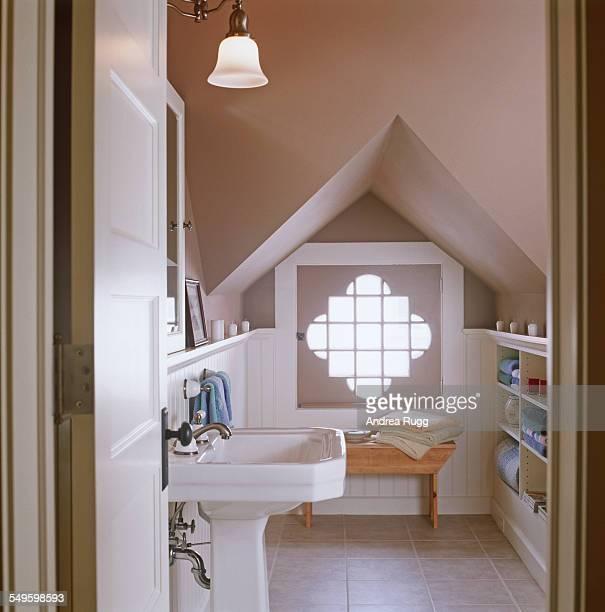 White and beige half-bath with artistic window