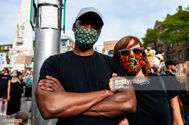 A white and black couple are holding their hands together during the massive solidarity protest against antiblack violence in the US and EU that took...