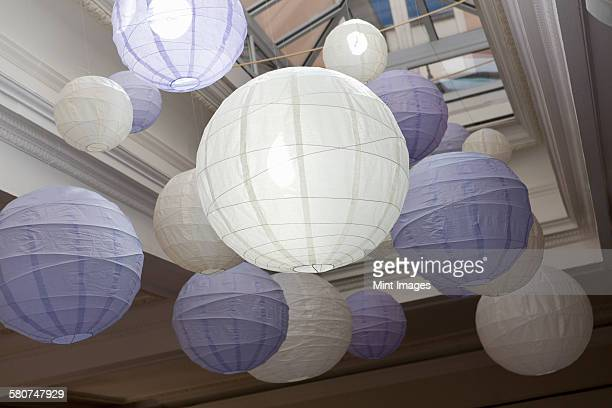 White and blue bamboo paper lanterns suspended from a ceiling.