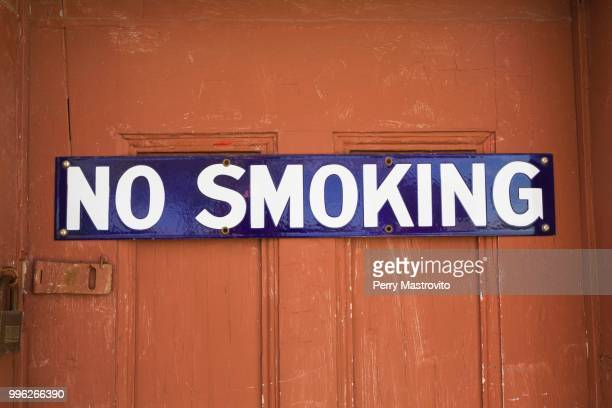 White and blue No Smoking sign on reddish brown wooden entrance door, background image