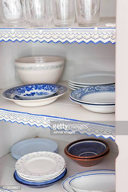 White and blue plates in cupboard