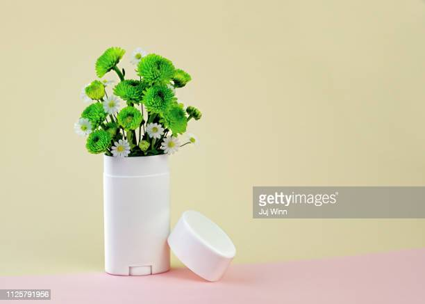 White and green flowers in a deodorant container