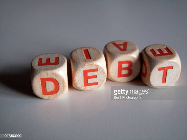 """White and orange scrabble dice spelling the word """"DEBT"""""""