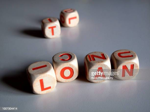 """White and orange scrabble dice spelling the word """"LOAN"""""""