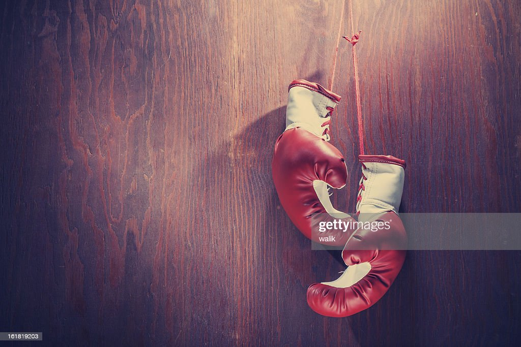 White and red boxing gloves hanging from wood background : Stock Photo