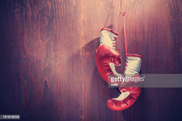 white and red boxing gloves hanging from wood background - boxing gloves stock photos and pictures