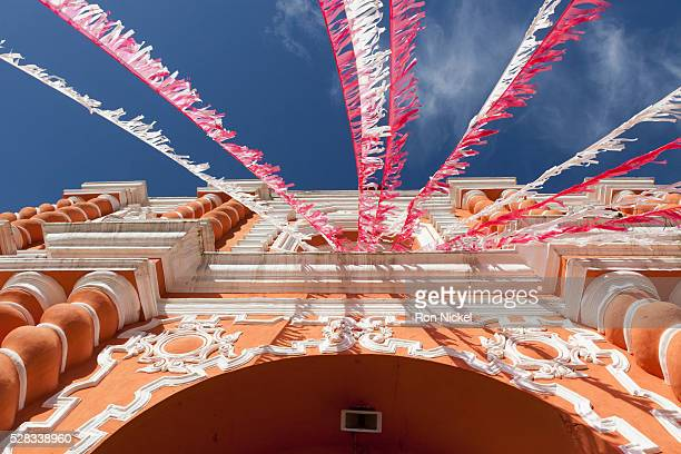 White and red streamers blowing in the wind strung above a building's doorway; guatemala city guatemala
