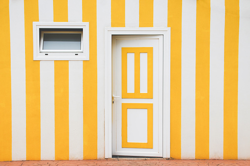 White and yellow door over a striped facade - gettyimageskorea