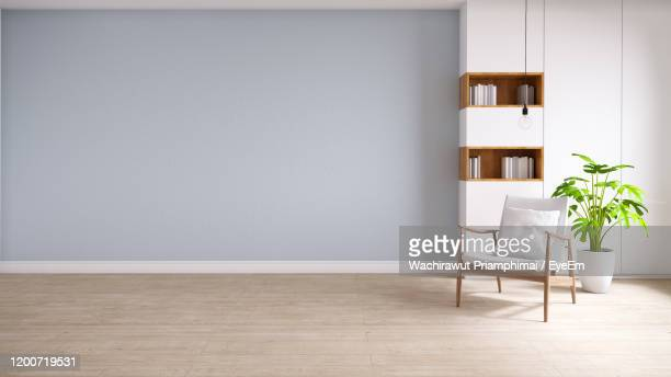 white armchair  on wood flooring and pastel blue wall, minimalist and vintage interior - leer stock-fotos und bilder