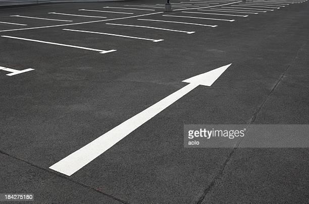 Weißen Pfeil auf ein leerer Parkplatz