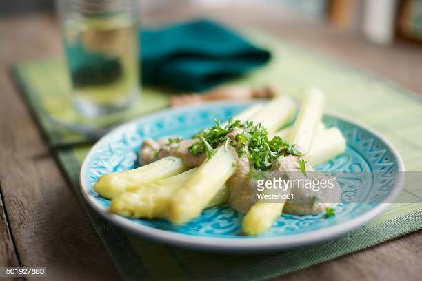 White asparagus with cashew cream sauce, garnished with chopped parsley
