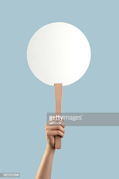 White auction placard with a hand holding it up