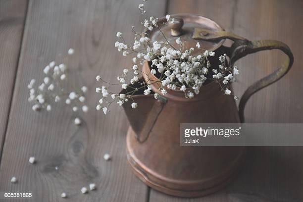 White baby's breath flowers (gypsophila) in a rustic copper pot