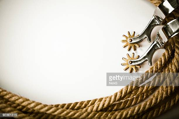 a white background bordered in ropes and spurs - lasso stockfoto's en -beelden