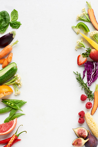 White background with colourful food border of raw fruit and vegetables 930069024