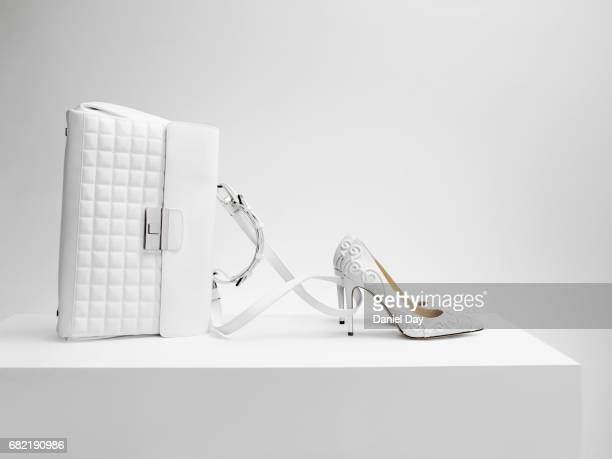 a white bag with white shoes in the form of cinderella's coach - clutch bag stock pictures, royalty-free photos & images