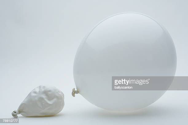 White balloon and deflated balloon on a white background