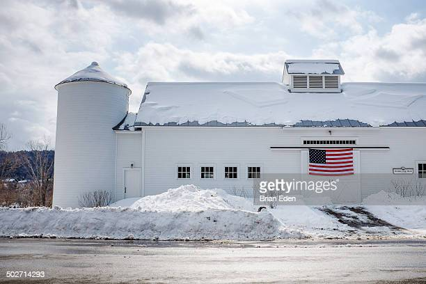 A white barn with an American Flag in Vermont