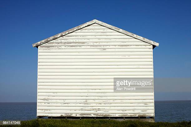 white beach hut standing alone - beach hut stock pictures, royalty-free photos & images