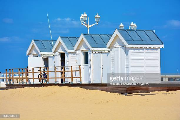 White Beach Huts On Sand Against Sky