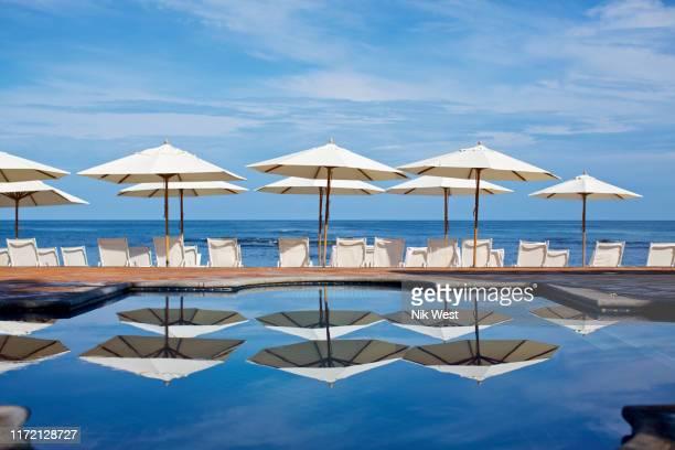 white beach umbrellas and lounge chairs at sunny ocean poolside, punta de mita, nayarit, mexico - cadeira recostável - fotografias e filmes do acervo