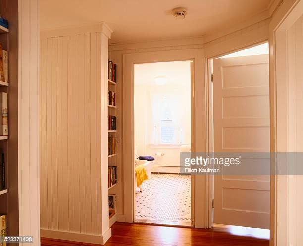 white beaded paneling in hallway leading to bathroom - badkamer huis stockfoto's en -beelden