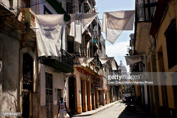 White bedsheets hang from a balcony in Old Havana against the backdrop of the Capitolio as a tribute to Havanas city historian late Eusebio Leal on...