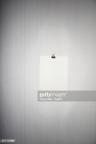 White blank paper hanging on white wall
